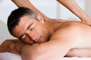 A man laying down on a massage table as he receives a massage