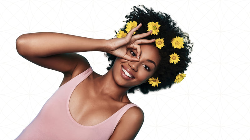 A young african american woman wearing eight yellow flowers on her hair as she makes a circle with her index and thumb and places is it around her eye as she looks through the middle