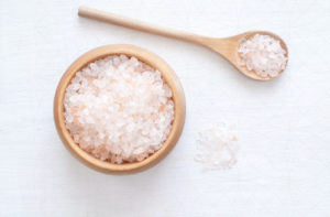 A wooden bowl and a wooden spoon both full of himalayan salt