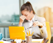A stressed woman working in front of a yellow computer