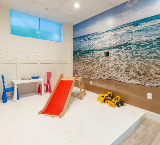 The children's room at the salt room orlando featuring a slide and playing area with a relaxing background of the ocean