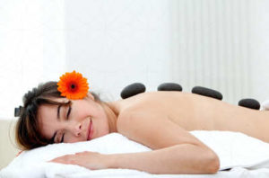 A young woman wearing an orange flower as she lays on a massage table with stones aligned in her back while she relaxes and smiles with her eyes closed