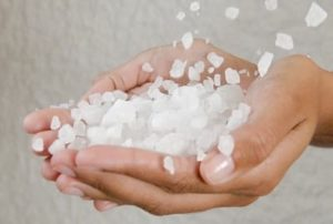 A woman's hands holding salt as it is being poured on her hands