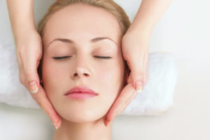 A young woman relaxing as she receives a facial massage