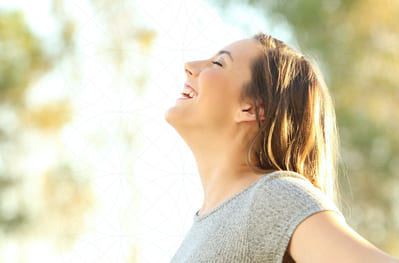 A woman smiling in joy as she feels relief from respiratory symptoms