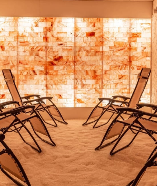 One of the rooms at The salt room orlando with six comfortable chairs and a wall of Himalayan salt tiles